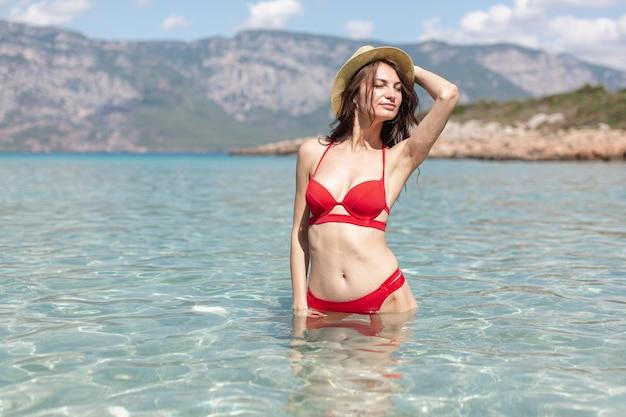 Sexy junge frau, die im meerwasser steht