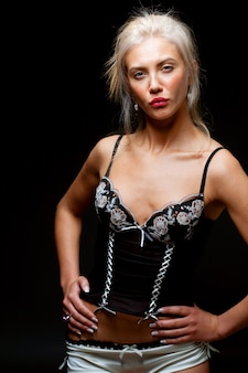 Sexy junge frau, die schwarze dessous auf schwarzem hintergrund trägt