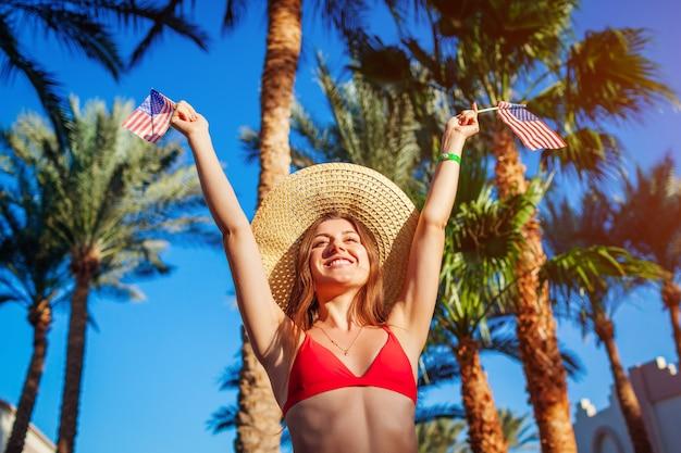 Sexy junge frau, die usa-flagge herein unter palmen hält.