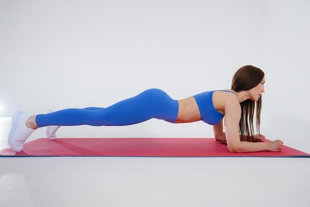 Sexy junge frau führt sportübungen durch. fitness, gesunder lebensstil.
