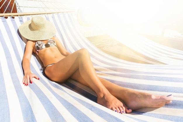 Sexy junge frau im bikini, die friedlich auf der strandhängematte auf dem seeweg ein sonnenbad nimmt. attraktive dame relax-modus in den sommerferien. mädchen, das unter heller sengender sonne auf der hängematte ein sonnenbad nimmt. strohhut im gesicht