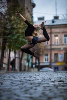 Sexy junge frau im pooltanzstil tanzen draußen in der straße