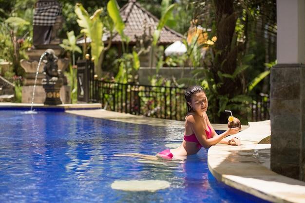Sexy junge frau im rosa badeanzug, der kokosnussgetränk im swimmingpool im urlaub hat.
