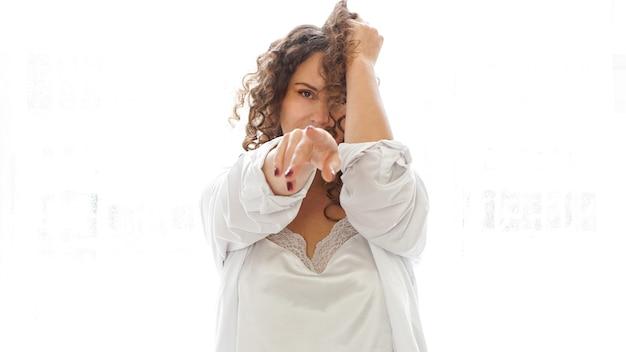 Sexy junge frau im weißen hemd im schlafzimmer, weißes licht aus dem fenster im hintergrund
