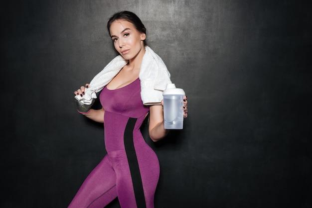 Sexy junge frau in der sportbekleidung stehend und wasserflasche zeigend
