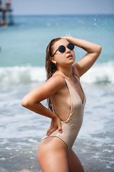 Sexy junge frau in einem geschlossenen badeanzug steht am sandstrand am meer. mädchen mit europäischem aussehen im urlaub am meer
