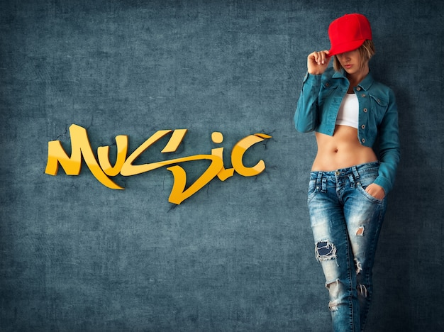 Sexy junge frau in trendiger kleidung an einer grunge-wand musikalische wand