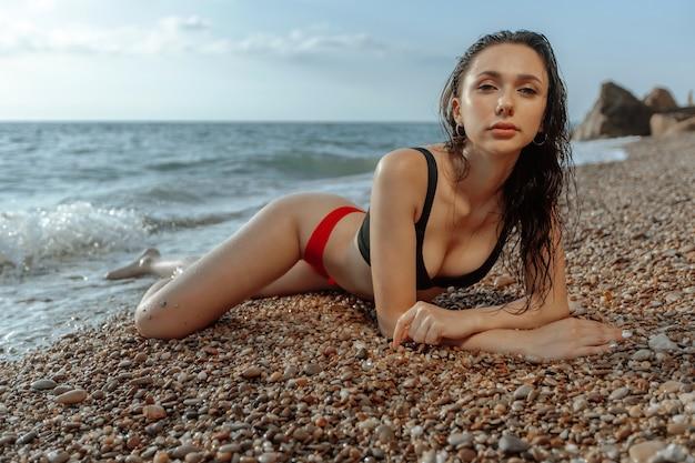 Sexy junge frau liegt am strand