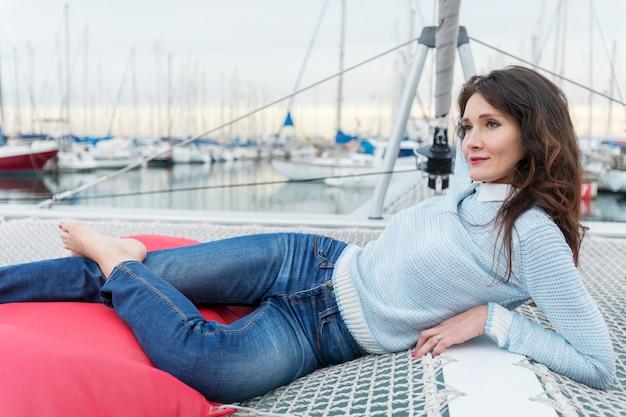 Sexy junge frau liegt auf yacht in jeans, während sie wegschaut