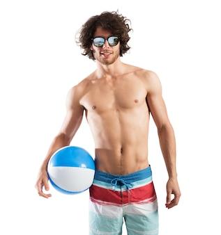 Sexy junge mit einem ball am meer