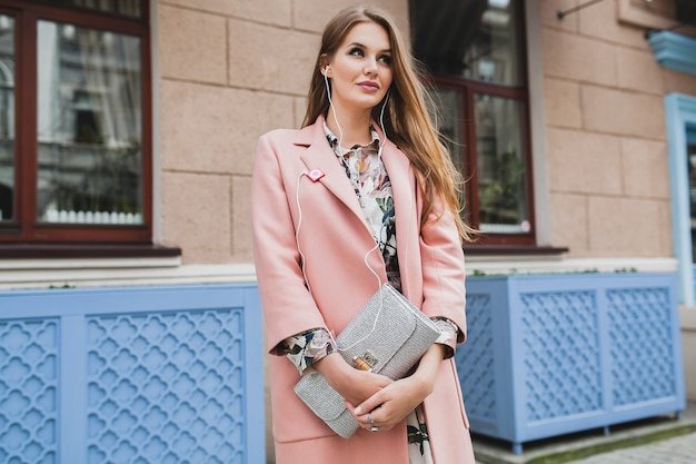 Sexy junge schöne stilvolle frau, die in der straße im rosa mantel geht, geldbörse in den händen hält, musik hört