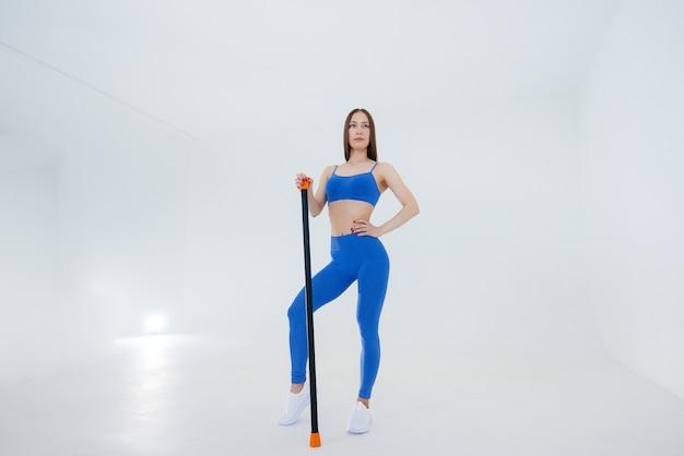 Sexy junge sportlerin führt sportübungen an einer weißen wand durch