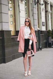 Sexy junge stilvolle schöne frau, die in der straße geht und rosa mantel trägt