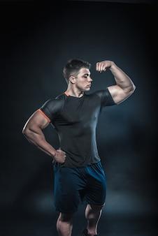 Sexy junger athlet, der auf einem schwarzen hintergrund im studio aufwirft. fitness, bodybuilding.