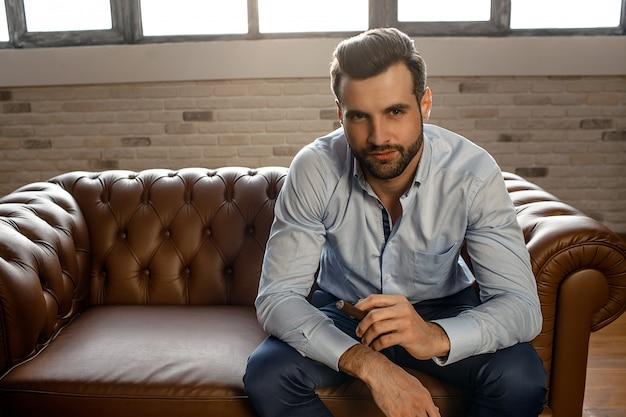 Sexy junger hübscher geschäftsmann sitzen auf sofa in seinem eigenen büro. er hält eine zigarre und schaut mit zuversicht direkt vor die kamera. sexy alfa männlich.