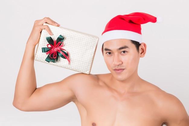 Sexy junger mann mit roter weihnachtsmann-hutausstattung, die seine geschenkbox hält.