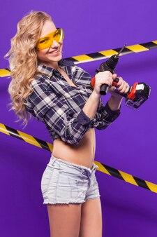 Sexy junges erbauermädchen im chechered hemd, in den gläsern und in den weißen kurzen hosen stehen mit elektrosäge