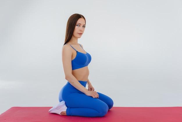 Sexy junges mädchen führt sportübungen auf einem weißen hintergrund durch.