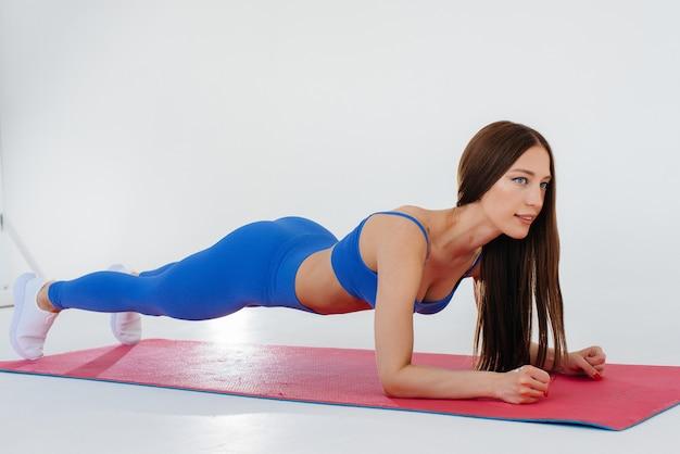 Sexy junges mädchen führt sportübungen auf einem weißen raum durch. fitness, gesunder lebensstil.