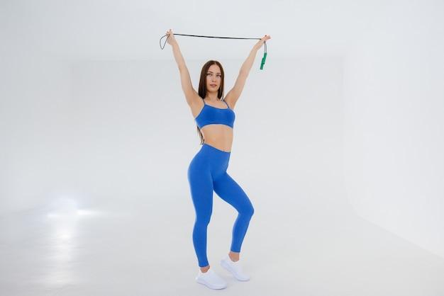 Sexy junges mädchen springendes seil in einem blauen trainingsanzug auf einem weißen hintergrund. fitness, gesunder lebensstil.