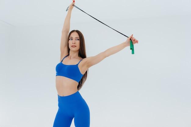 Sexy junges mädchen springendes seil in einem blauen trainingsanzug auf einem weißen hintergrund.