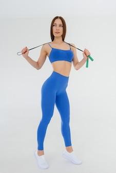 Sexy junges mädchen springendes seil in einem blauen trainingsanzug auf einer weißen wand. fitness, gesunder lebensstil.