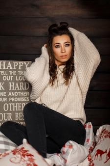 Sexy junges modellmädchen im modischen strickpullover auf einem bett nahe einer holzwand