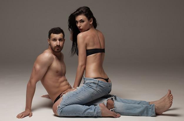 Sexy junges paar. schönes sexy paar verliebt in grauen hintergrund gekleidet in blue jeans.