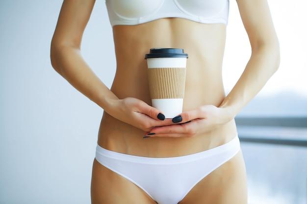 Sexy körper der frau, die kaffeetasse hält