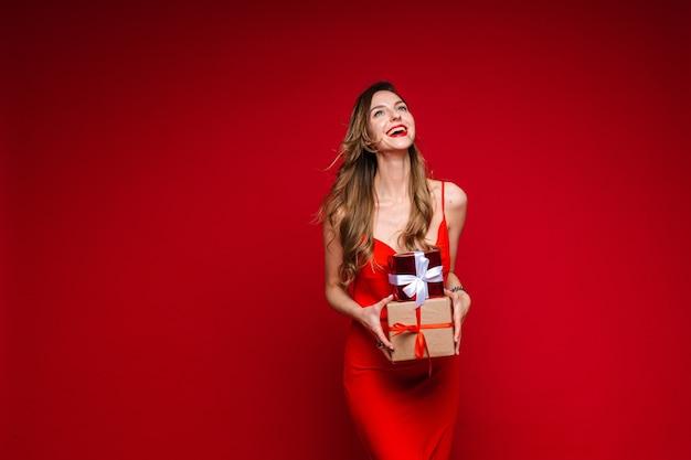 Sexy lachende frau im rot mit zwei geschenken.