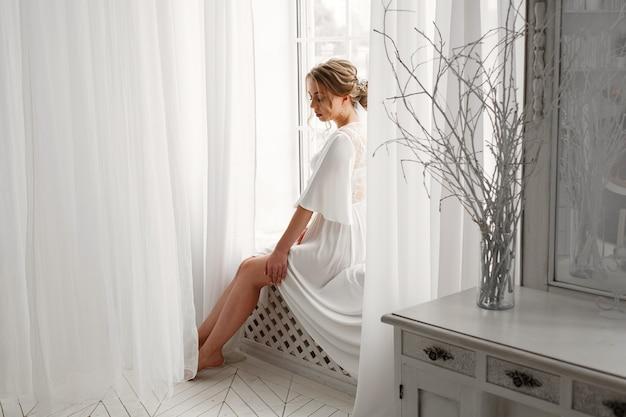 Sexy lächelnde blonde braut in unterwäsche im schlafzimmer. morgen der schönen braut im hotelzimmer mit stilvollem interieur. junge frau in weißer unterwäsche oder nachthemd auf weißem nahe gebotsfenster