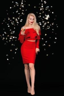 Sexy lächelnde junge frau mit glas champagner im roten kleid, das im studio aufwirft.