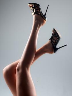Sexy lange frauenbeine in den modeschuhen. erotische körpersprache.