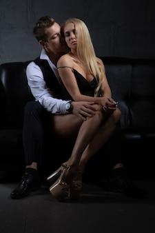 Sexy leidenschaftliches paar in eleganten abendkleidern umarmt auf der couch sitzend. modenschau.