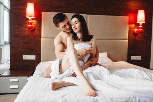 Sexy liebespaar umarmt auf großem weißem bett nach intimität. intime spiele im schlafzimmer, sexliebhaber beziehung