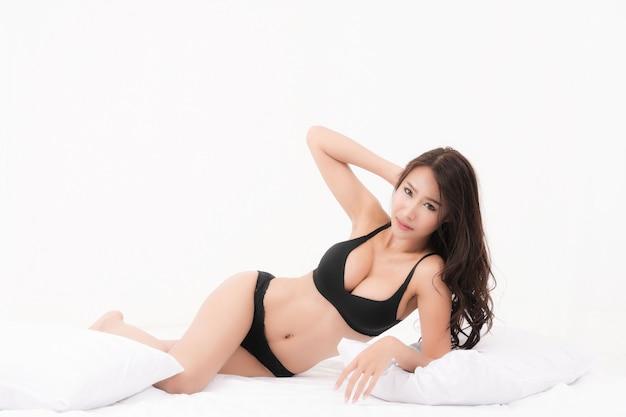 Sexy lifestyle-porträt der schönen verführerischen braunen langhaarigen sexy schwarzen unterwäsche der jungen frau im weißen schlafzimmer. konzeptmode sexy im bett. studioaufnahme.