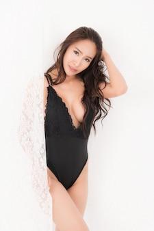 Sexy lifestyle-porträt der schönen verführerischen jungen frau braun langhaarig im schwarzen sexy body stehen an weißen vorhängen. konzeptmode sexy im schlafzimmer. studioaufnahme.