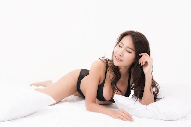 Sexy lifestyle-porträt der schönen verführerischen jungen frau braune langhaarige sexy schwarze unterwäsche im weißen schlafzimmer