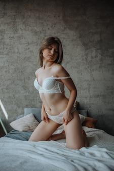 Sexy mädchen, das auf bett in weißen dessous sitzt