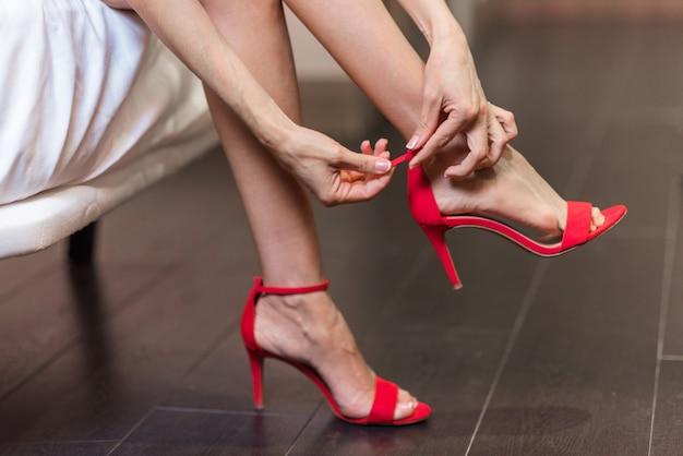 Sexy mädchen, das ihre roten schuhe der hohen absätze an setzt