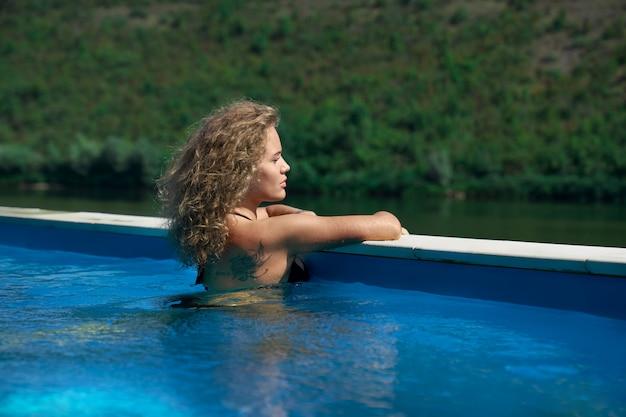 Sexy mädchen, das im schwimmbad auf natur ruht.
