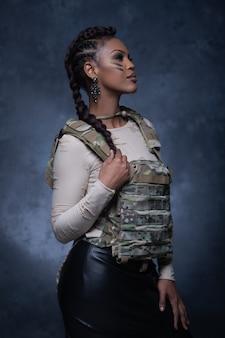 Sexy mädchen, das militärische artweste trägt, die aufwirft und in die kamera im studio schaut