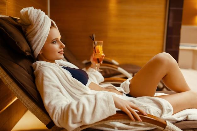 Sexy mädchen, das mit cocktail im spa-stuhl entspannt