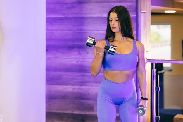 Sexy mädchen, das sportübungen mit hanteln in der turnhalle in einem blauen sportanzug tut