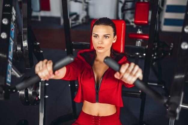 Sexy mädchen, das übungen in ihren brustmuskeln im simulator tut.