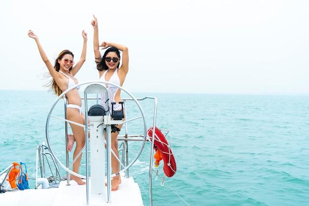 Sexy mädchen des bikinis stehen und tanzen mit fahrerhandlenkrad auf bootsyacht