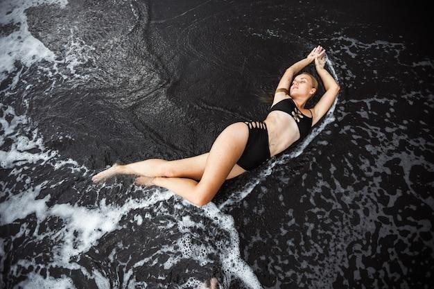 Sexy mädchen im badeanzug liegt in den wellen auf dem schwarzen sand blick von oben