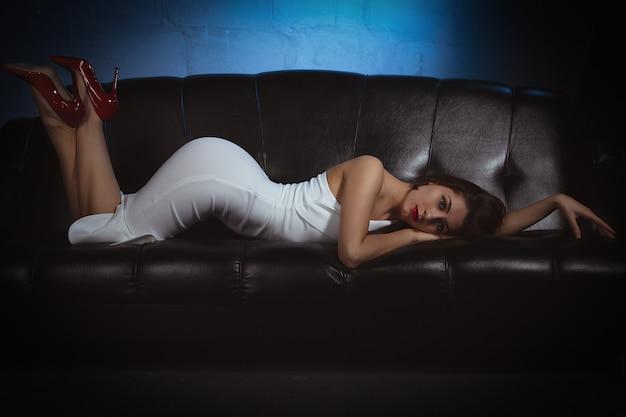 Sexy mädchen im weißen kleid und in den roten schuhen, die auf schwarzer couch liegen