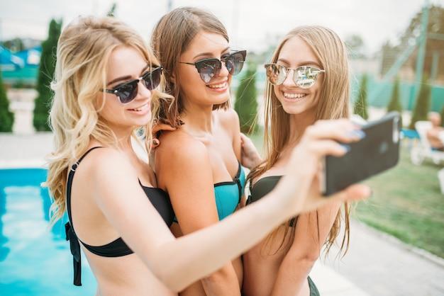 Sexy mädchen in badeanzügen machen selfie in der nähe des pools