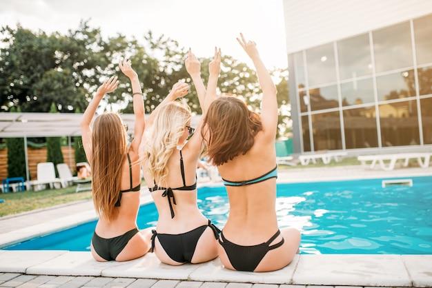 Sexy mädchen in badeanzügen sitzen am pool, rückansicht. urlaub im resort. gebräunte frauen, die sich in der nähe des schwimmbades sonnen